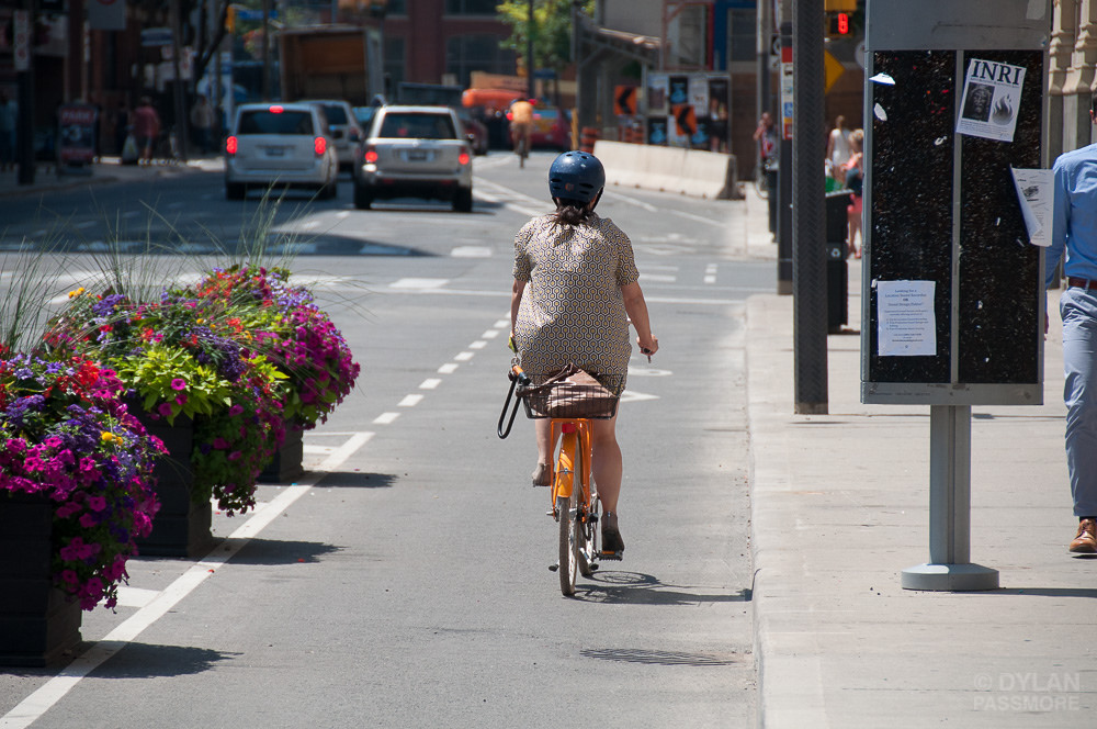 Woman cycling on Richmond protected bike lane (Photo credit: Dylan Passmore)